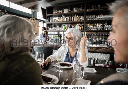 Happy senior women friends dining in restaurant Photo Stock