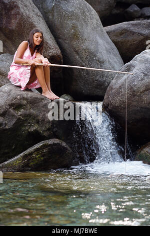 Jeune fille assise sur un rocher à la pêche dans un ruisseau de montagne Photo Stock