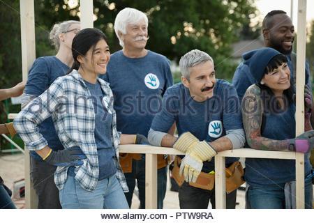 Aide à construire les bénévoles souriants house Photo Stock