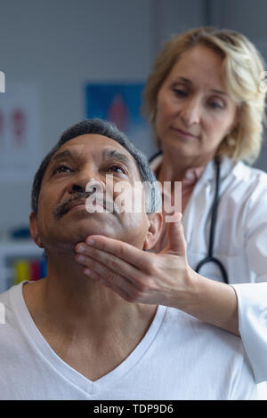 Vue avant du Caucasian female doctor examining patient mâle de race mixte à l'hôpital de cou Photo Stock