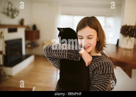 Affectueux girl holding black cat Photo Stock