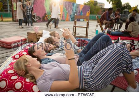 Teenage Girls hanging out, relaxant et avec les téléphones intelligents en parc urbain Photo Stock