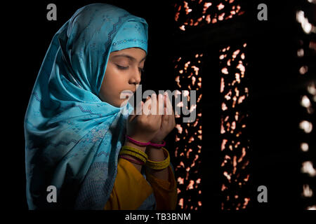 Jeune musulmane portant le hijab priant dans le noir avec les yeux fermé Photo Stock