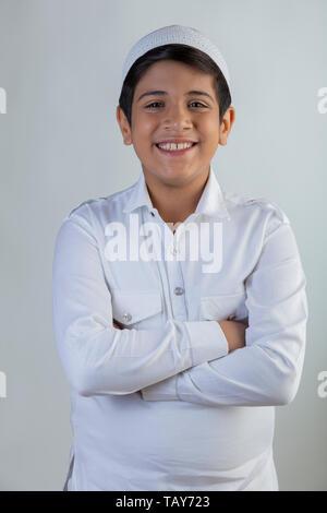 Jeune garçon musulman wearing cap folding hands and smiling Photo Stock