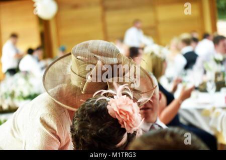 Mère de la mariée de porter un grand chapeau parle à un invité de mariage en privé à Photo Stock