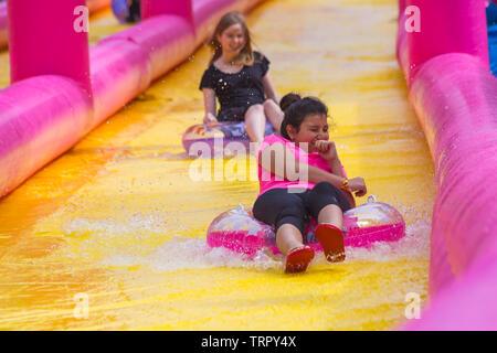 Assis sur les filles s'amusant sur les anneaux gonflables toboggan géant, toboggan, à Bournemouth, Dorset UK en Juin Photo Stock