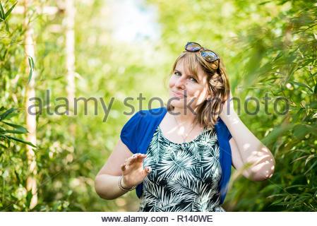 Portrait of a smiling woman standing contre des plantes Photo Stock