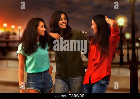 Trois amies debout à l'extérieur en soirée et de parler Photo Stock