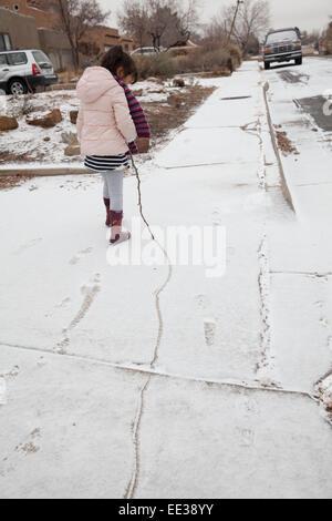 Petite fille de cinq ans trace une ligne dans la neige avec un bâton. Photo Stock