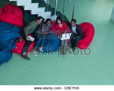 Smiling business gens assis dans des sièges-sacs Photo Stock