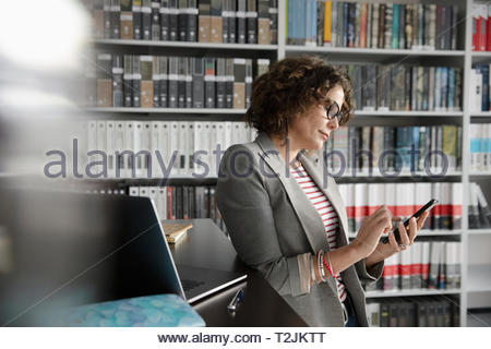 Femme d'intérieur à l'aide de smart phone in office Photo Stock