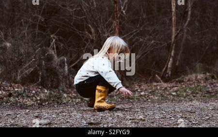 Enfant ramasser des pierres Photo Stock