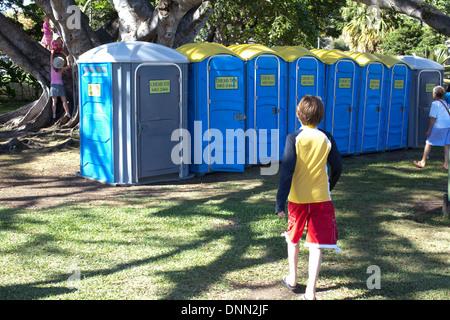 Garçon de dix ans autour d'utiliser une salle de bains privative en plein air, rangée de porta des pots, festival en plein air. Photo Stock