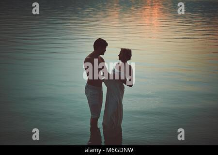 La femme et l'homme serra en eaux sombres au coucher du soleil. Amour et romance Photo Stock