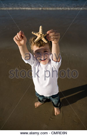 Garçon tenant une étoile de mer Photo Stock