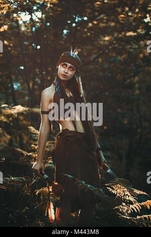 Chasseresse avec couteau et tomahawk. Portrait de la forêt Photo Stock