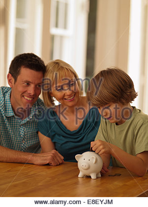 Parents fils mettait pièce dans piggy bank Photo Stock