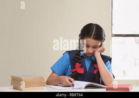 Girl sitting in rural livre de lecture en classe Photo Stock