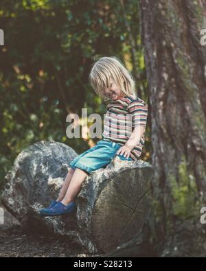 Bénéficiant de l'enfant assis sur log Photo Stock