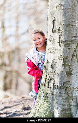 Girl behind tree Photo Stock