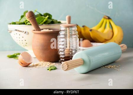 Ingrédients pour la cuisson des épinards ou des pancakes à la banane ou la cuisson des épinards ou des muffins aux bananes- avoine, bananes, rouleau à pâtisserie, les œufs, les épinards, le miel Photo Stock