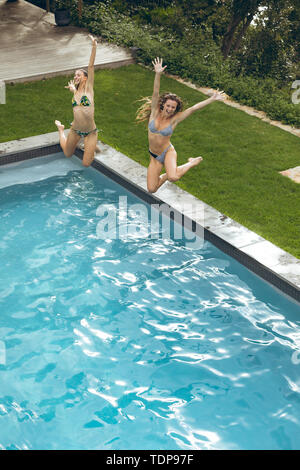 High view of happy female friends sauter dans la piscine de l'arrière-cour Photo Stock