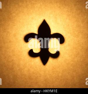 Silhouette en contre-jour de fleur-de-lis shape cut out contre ton brun, papier avec spot mettez en surbrillance. Photo Stock