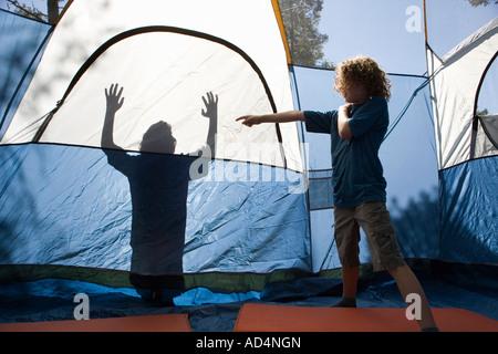 Un jeune garçon en montrant une ombre sur une tente Photo Stock
