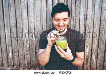 Portrait of a smiling young man drinking à partir d'un bocal en verre Photo Stock