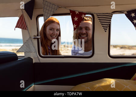 Portrait of happy young Caucasian couple looking at camera près de camping-van at beach Photo Stock