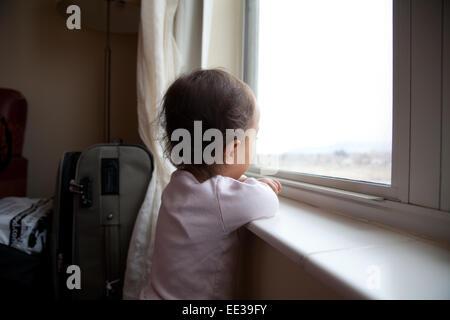 Enfant de deux ans qui tombent à travers la neige montres fenêtre. Photo Stock