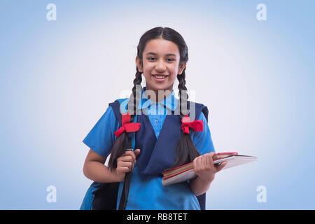 Portrait de school girl holding book et sac Photo Stock