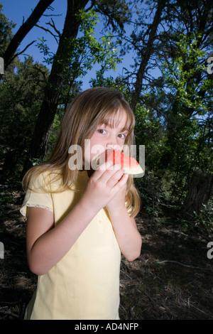 Une jeune fille manger un morceau de pastèque dans une forêt Photo Stock