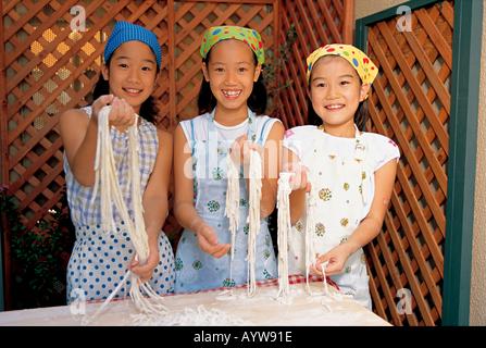 Trois jeunes filles faisant des pâtes et nouilles Photo Stock
