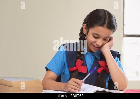 La fille rurale, en uniforme d'sitting at table reading book Photo Stock