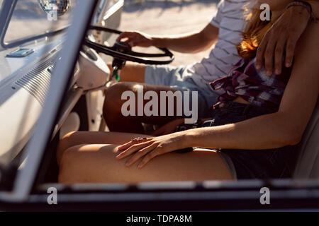 Mid section of Caucasian man sur le siège avant de camper van at beach Photo Stock