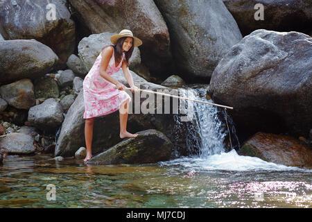 Smiling girl pêche dans un ruisseau de montagne. Amusement et relax Photo Stock