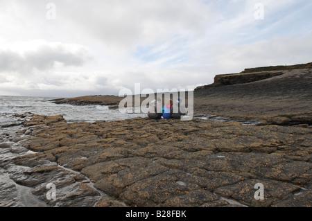 Trois jeunes adolescents 2 garçons et une fille âgés de 8 à 10 assis sur les roches par la mer Photo Stock