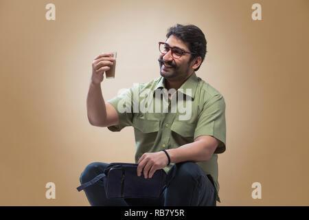 Smiling man wearing eyeglasses tenant une petite pochette dans une main et à la recherche à un verre de thé dans son autre main. Photo Stock
