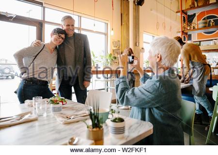 Senior woman photographing mari et sa fille dans le café Photo Stock