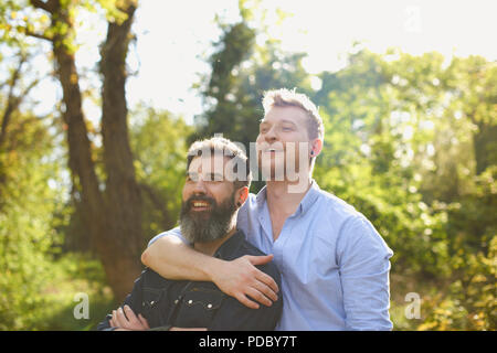 Homme affectueux gay couple hugging in sunny park Photo Stock