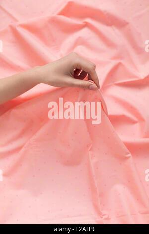 Main de femme tenant un tissu rose Photo Stock