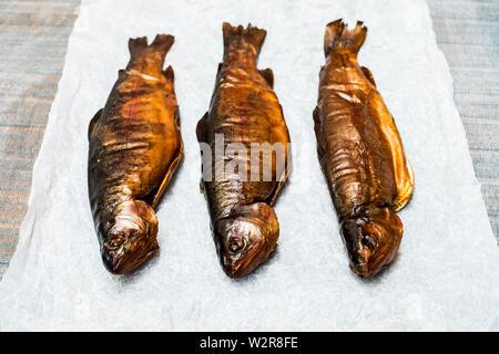 High angle portrait de trois truites entières fraîchement fumé sur un papier blanc. Photo Stock