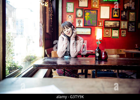 Une jeune femme assise à une table dans un café à Manchester. Photo Stock