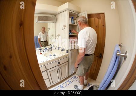Quatre-vingts ans, homme, et recherches de ses médicaments dans son armoire à pharmacie, accueil, salle de bains, United States. Photo Stock