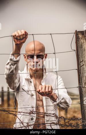 Jeune homme en colère avec tête à tête, debout près de grillage Photo Stock