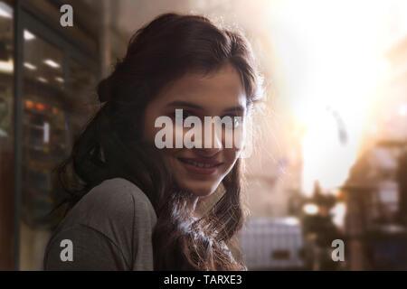 Portrait d'une jeune femme debout à l'extérieur avec la lumière du soleil en arrière-plan Photo Stock