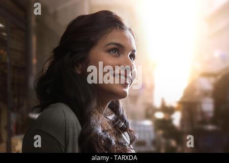 Vue latérale d'une jeune femme debout à l'extérieur à l'écart Photo Stock