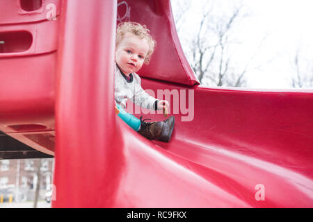 Toddler playing on slide Photo Stock