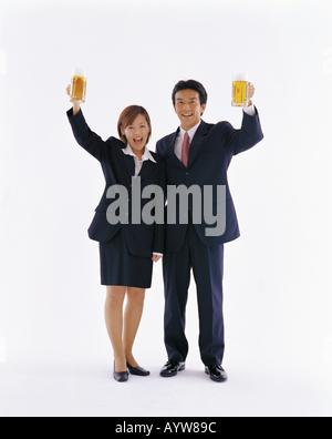 L'homme et de la femme au bureau grâce à la bière dans les mains Photo Stock